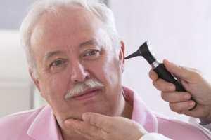 Doctor checking elderly man's ear