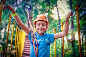 Little boy standing on a ropes-course bridge