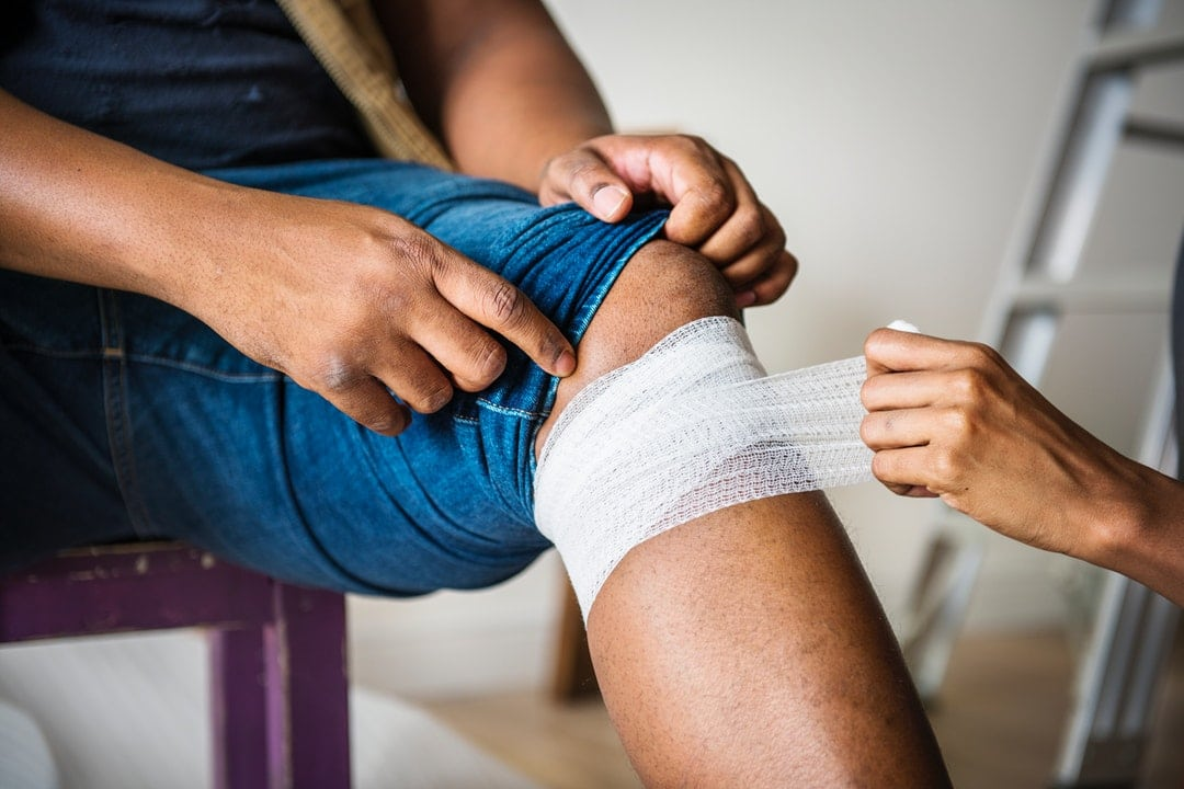 Man's upper leg being wrapped with bandage