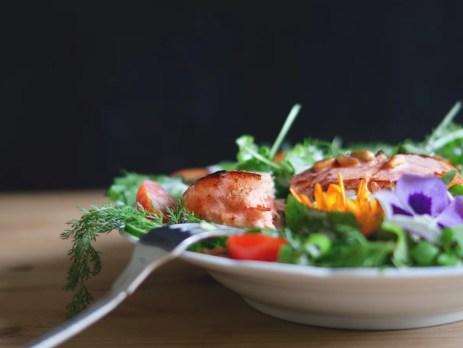 Rucola-Salat mit Tomaten, Blüten, Hähnchenbrust, auf einem Teller angerichtet. Hähnchenbrust ist ein Lebensmittel mit Vitamin B12.