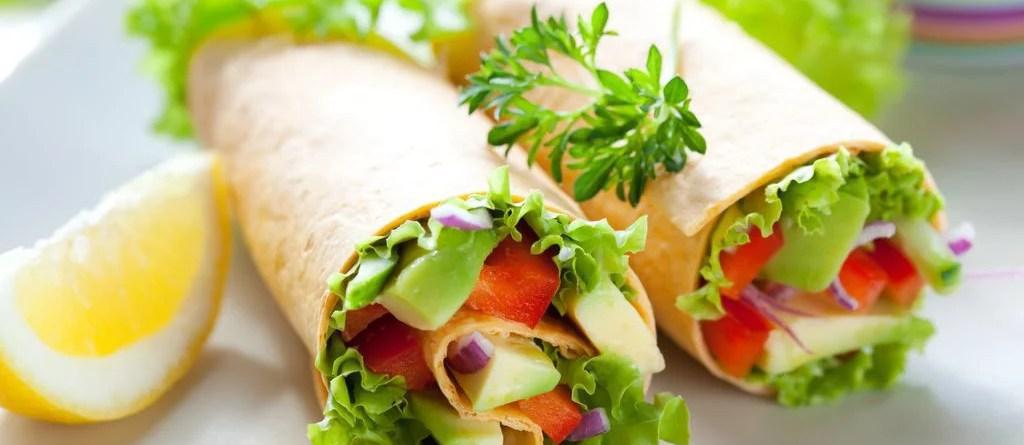 Wraps mit grünem Salat, Tomaten und Käse auf einem Teller angerichtet. Käse ist ein Lebensmittel mit Vitamin B12.
