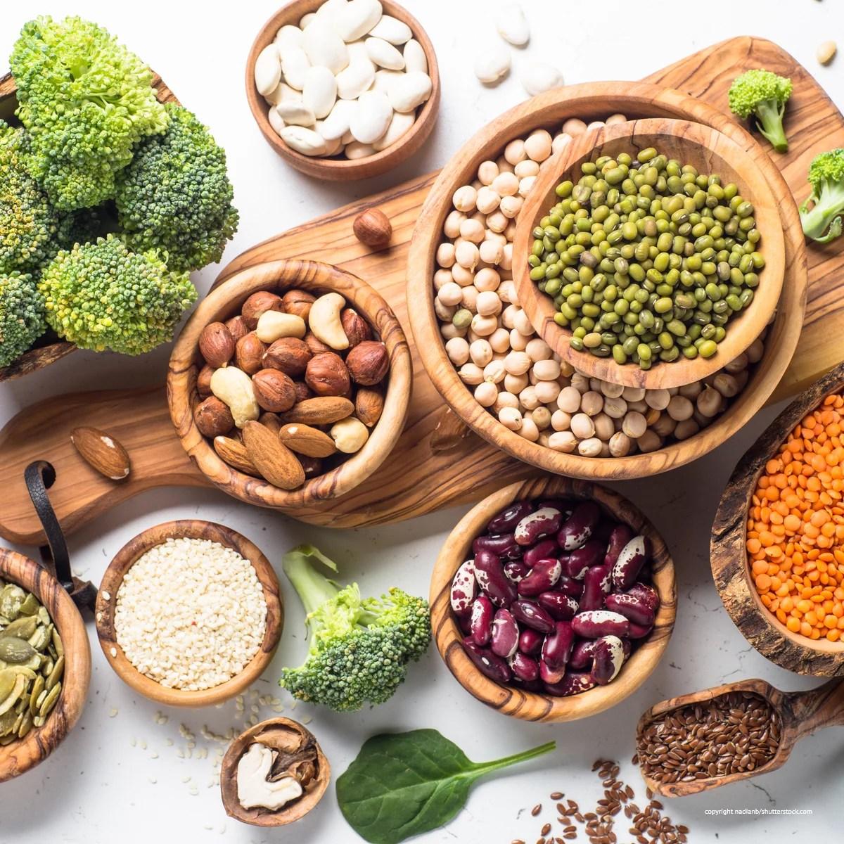 Hülsenfrüchte, Nüsse und Samen auf einem Küchenbrettchen dekoriert. Veganen Lebensmittel fehlt Vitamin B12.