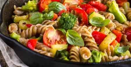 Eine leckere Gemüsepfanne mit Brokkoli, Tomaten, Hafer-Nudeln und Geflügel liefert Vitamin B12 und Eisen.