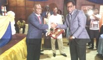 Sir Kenny Okolugbo (R) receiving the award from Secretary of the Delta state Government, Comrade Ovuzourie Macaulay