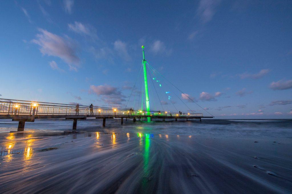 """Die """"Hohwachter Flunder"""" im Lichtermeer: Mit ihrem schon von weitem sichtbaren, 24 Meter hohen Stahlpylon ist die Seebrücke das Wahrzeichen des Ostseeheilbads Hohwacht - Ostseeküste Schleswig-Holstein"""