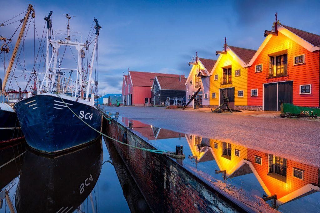 Zoutkamp, ein malerisches Fischerdorf mit einem Kai voll farbenfroher Häuser und einem Hafen voller Fischerboote.