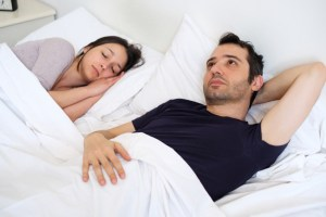 sad man in bed with sleeping spouse