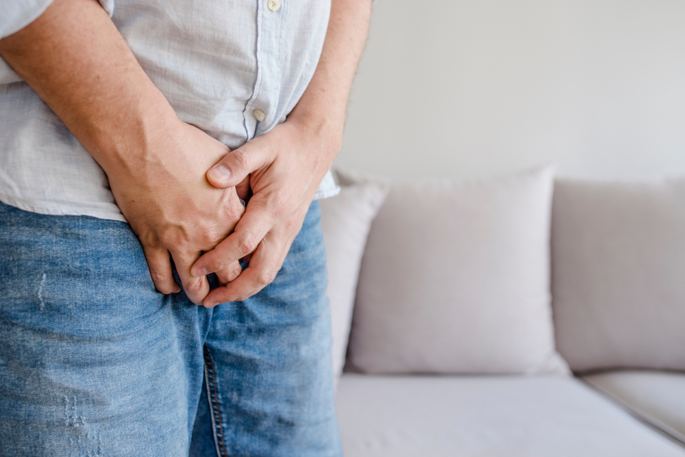 Man with hands holding his crotch, he wants to pee - urinary incontinence concept.