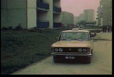 """Taksówka (w tej roli Fiat 125p) na zaimprowizowanym na potrzeby filmu """"Skradziona kolekcja"""" postoju na ulicy Wiolinowej. Kadr z filmu w reż. Jana Batorego."""