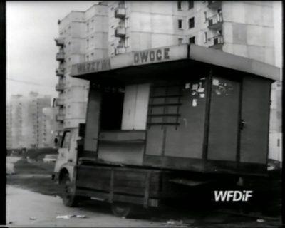 """Klasyczna budka z owocami i warzywami stawiana przed blokiem na Koncertowej. W tym miejscu wychodzimy dziś z metra. Kadr z filmu """"Skupisko"""", reż. J. Gębski. Prod. WFDiF"""