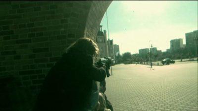 """Ruch stop - pan zaczyna strzelać. Ukryty przy bocznym wejściu do kościoła Wniebowstąpienia prowadzi ogień w kierunku placyku z fontanną. Kadr z serialu """"Pitbull"""", odc. 16."""