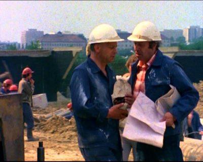 """Rok 1976. Za inżynierem Małkiewiczem (Leon Niemczyk) buduje się wiadukt Doliny Służewieckiej przy Kopie Cwila. W tle budynki uniwersyteckie na Służewcu. Kadr z serialu """"Czterdziestolatek""""."""