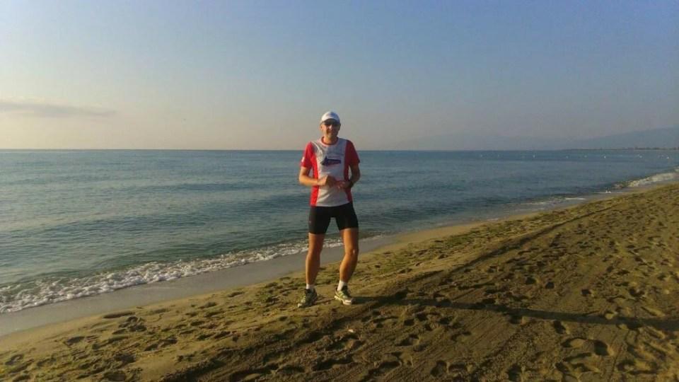 koniec treningu na plaży, wschodzące słońce oświetla biegacza