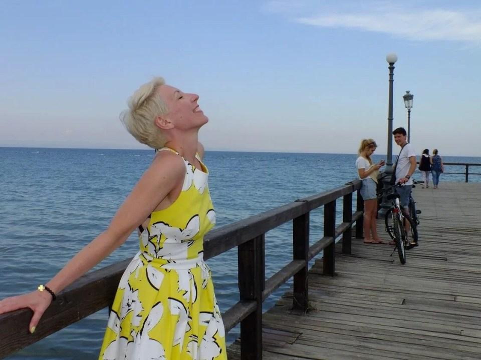 greckie wakacje i szczęśliwa kobieta na molo podziwiana przez mężczyznę