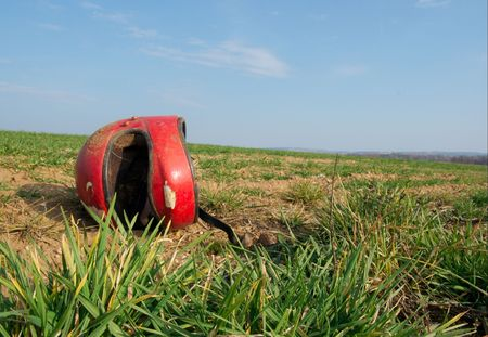 motorcycle crash: Red broken helmet on an agricultural field