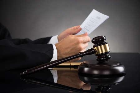 Close-up Do Juiz Segurar Document Com Gavel Na Mesa Banco de Imagens - 43938034