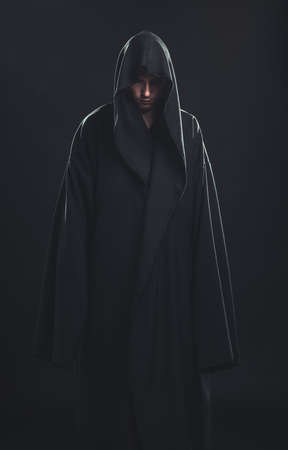 demons: Portrait of a Man in a black robe on a dark background