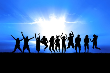 Silhouettes of a celebratory group jump in field of grass, bright sun behind Stock Photo - 14350172