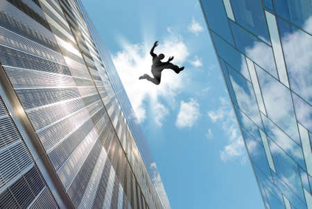 jumping: Man jumping over building roof against blue sky background Stock Photo