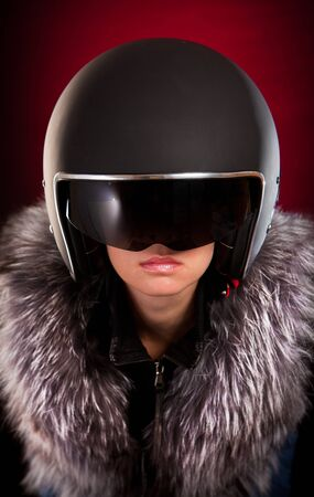 red motorcycle: Biker girl in a helmet on a red background