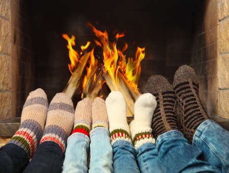 home: Feets of a family wearing woolen socks warming near the fireplace Stock Photo