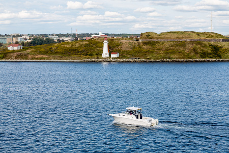 White lighthouse on bay near Halifax, Nova Scotia with white yacht Stock Photo - 41815562