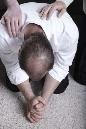 laying hands: Man praying on his knees