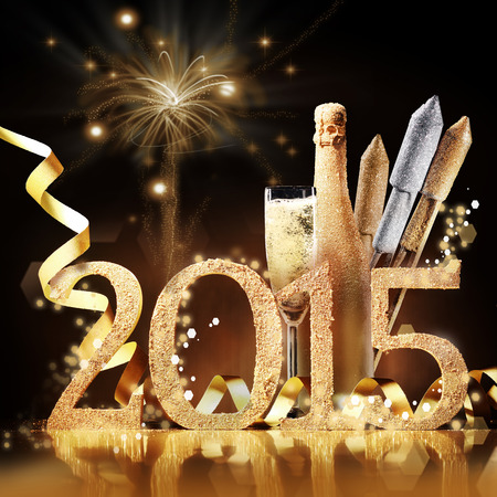 2015 New Yeas Eve celebration still life in elegant gold with the date, a flute and bottle of champagne and rockets in front of a brown background with a pyrotechnic display of bursting fireworks Stock Photo - 33635618