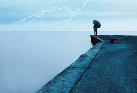 man rain wind: woman on the dock looks to the sea Stock Photo