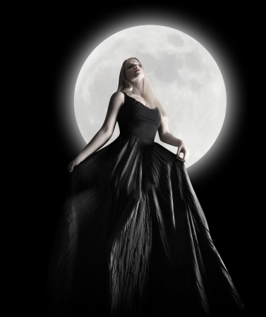 A woman is wearing a long black dress moving in the dark night against a full moon for a fashion or mystery concept. Stock Photo - 17892581