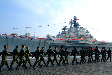 chinese military: Warship in the bay and chinese Soldier training. Editorial