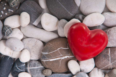 love and memories: Red heart among river pebble stones