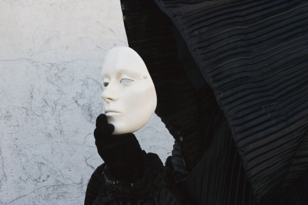 Black figure in the hood, taking off white face mask. Venice. Masquerade Stock Photo - 2415945