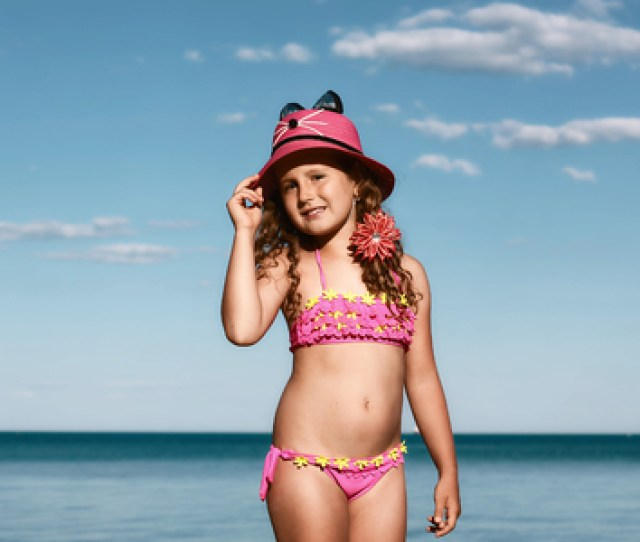 Young Curly Girl In A Pink Swimsuit Relaxing On The Beach In The Hat Black