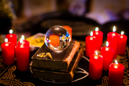 witchcraft: Crystal ball to prophesy or esoteric clairvoyance during a Seance in the candle light Stock Photo