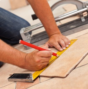 Laying Ceramic Floor Tiles   Man Kneeling And Marking Tile To     Laying ceramic floor tiles   man kneeling and marking tile to be cut   closeup on
