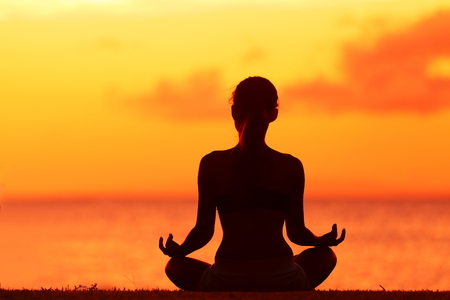 Zen yoga woman doing meditation on beach - wellness concept. Female silhouette relaxing sitting at sunset background meditating at ocean retreat. Summer orange sunrise sky. Stock Photo - 37924086