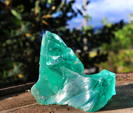 quartz crystals: Large turquoise green quartz rock sits on a barrel top in Wyoming.