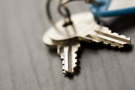 key: Macro Shot of Conceptual House Keys on Top of Wooden Table