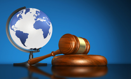 LAW ICONS: International law systems, justice, human rights and global business education concept with world map on a school globe and a gavel on a desk on blue background.