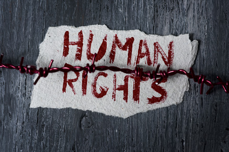 concentration camps: high-angle shot of a barbed wire and a piece of paper with the text human rights handwritten in it on a rustic wooden surface Stock Photo