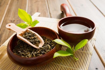 green tea: tea and tea leaves on bamboo mat on wooden table