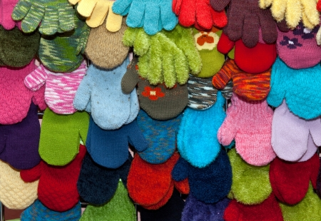warm clothing gloves: showcase childrens mittens and gloves colored background Stock Photo