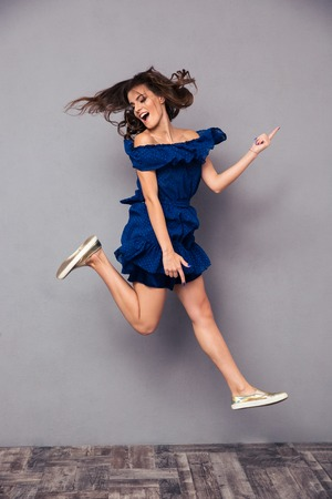 happy woman: Portrait of a funny cheerful woman jumping on gray background Stock Photo