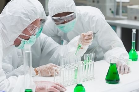 Two chemists experimenting with the green liquid in the laboratory Stock Photo - 15591813
