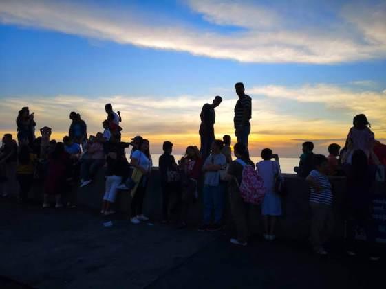 マニラ湾に沈む夕日を見れるMOA EYEの中からの夕日を待つ人は堤防で立つのは禁止