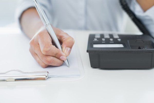 A person actively listening to a client ready to take notes