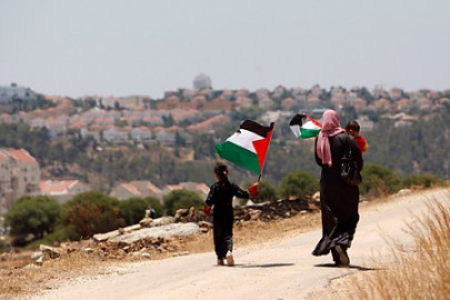 A Palestinian woman and a child walk together on their way to a celebration for land that was recently returned to the Palestinians after Israel rerouted a section of it's controversial barrier which separates the Jewish settlement of Modiin Illit (seen in the background) and the West Bank village of Bilin, near Ramallah July 1, 2011. REUTERS/Mohamad Torokman (WEST BANK - Tags: POLITICS)