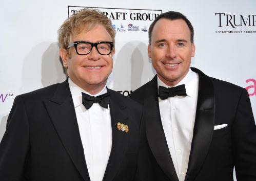 FILE - In this photo, Sir Elton John, left, and husband David Furnish attend the Ninth Annual Elton John AIDS Foundation benefit 'An Enduring Vision' at Cipriani Wall Street in New York. John and Furnish have become parents to a 7-pound, 15-ounce baby boy born on Christmas Day. The news was first reported Monday night by USMagazine.com and confirmed to The Associated Press by John's Los Angeles-based publicist. (AP Photo/Evan Agostini, File)