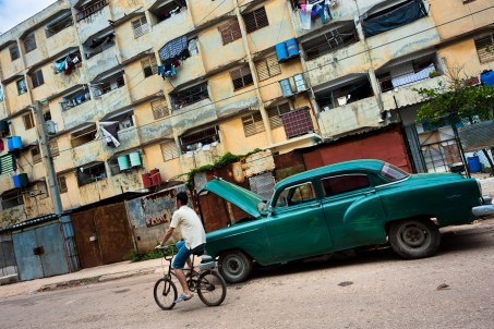 """A young Cuban man rides a bicycle in front of the huge apartment blocks in Alamar, a public housing periphery of Havana, Cuba, 9 February 2011. The Cuban economic transformation (after the revolution in 1959) has changed the housing status in Cuba from a consumer commodity into a social right. In 1970s, to overcome the serious housing shortage, the Cuban state took over the Soviet Union concept of social housing. Using prefabricated panel factories, donated to Cuba by Soviets, huge public housing complexes have risen in the outskirts of Cuban towns. Although these mass housing settlements provided habitation to many families, they often lack infrastructure, culture, shops, services and well-maintained public spaces. Many local residents have no feeling of belonging and inspite of living on a tropical island, they claim to be """"living in Siberia""""."""